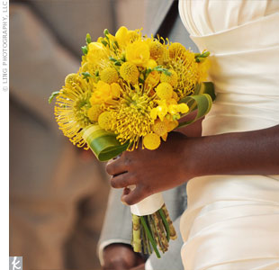 A bold protea, freesia and craspedia bouquet provided an instant pop of color against the brides off-white gown.