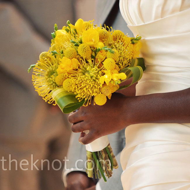 A bold protea, freesia and craspedia bouquet provided an instant pop of color against the bride's off-white gown.