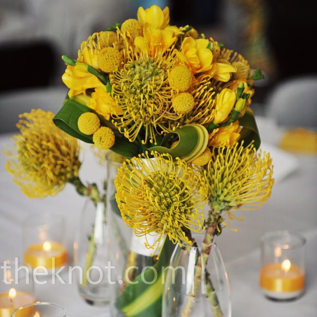 Modern arrangements of pincushion protea, craspedia, freesia and banana leaves were surrounded by small ribbon-wrapped votives.