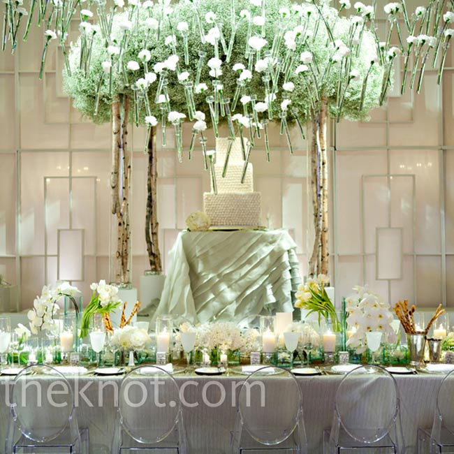 For visual cohesion between the ceremony and reception design, Todd created a cake display similar to the ceremony arbor and accented it with ghost chairs and single-stem vases to make the flowers appear as if they were floating.