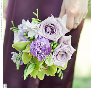 Danielle chose A-line dresses in a plum hue for her bridesmaids, who walked down the aisle with bouquets of roses, orchids, and green hypericum berries.