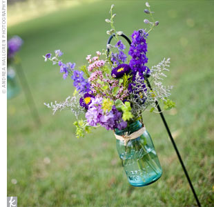 Ball jars wired to shepherd's hooks were filled with wildflowers to seamlessly blend with the house's natural landscaping.