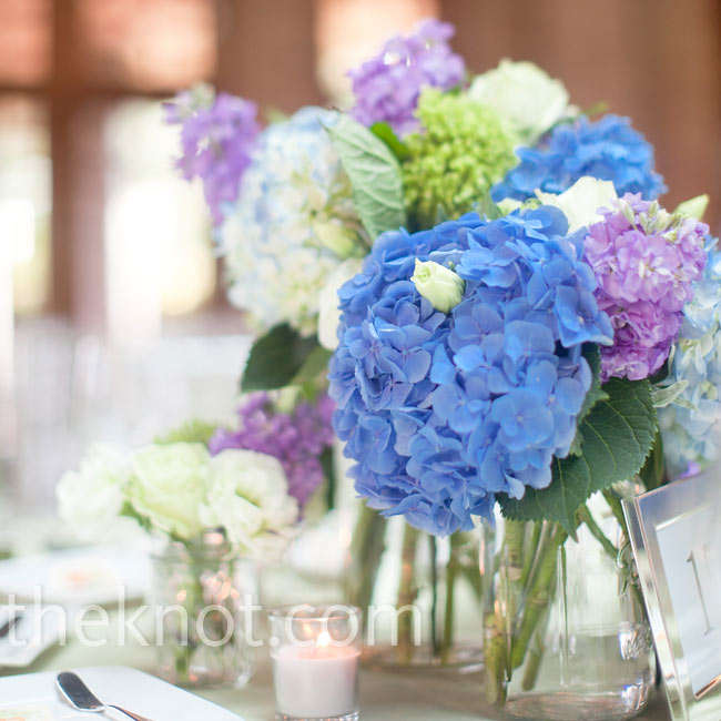 The centerpieces included both dark-blue (Dutch) and light-blue (South American) hydrangeas arranged in Mason jars with green hydrangeas, tea roses, lisianthus and stock.