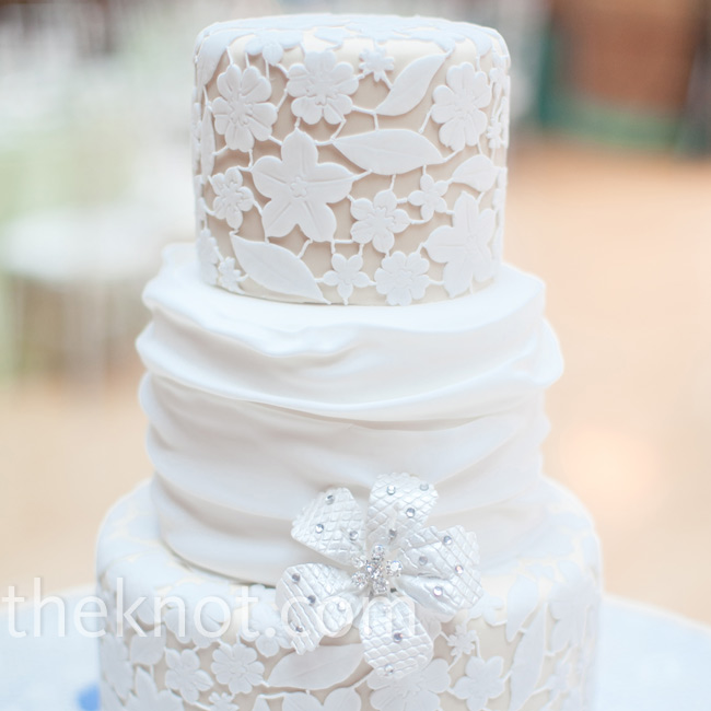 Dark-ivory fondant with an off-white fondant lace covering decorated the top and bottom tiers, while a fondant swag wrapped the middle one. A silver sugar flower completed the look.