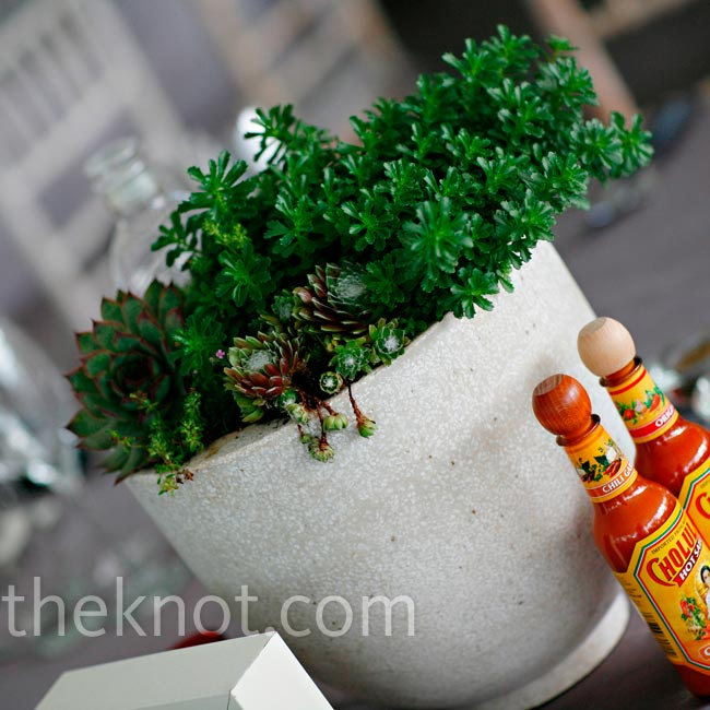 Instead of traditional vases of flowers, urns filled with rich green succulents decorated the tables.