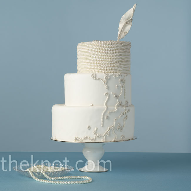 Delicate sugar pearls, off-center tiers and a fun sugar feather to