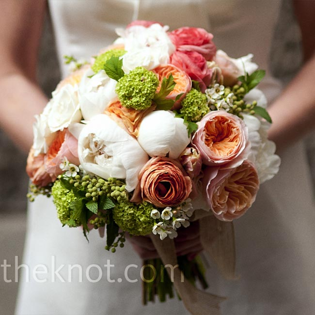 Caki's bouquet was made up of Juliet garden roses, ranunculus, viburnum, peonies and wax flowers in shades of white and coral and tied with burlap ribbon.