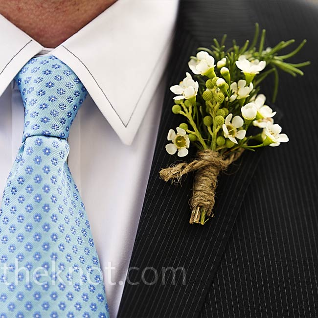 Clusters of wax flowers and fragrant rosemary tied with twine served as simple and rustic boutonnieres.