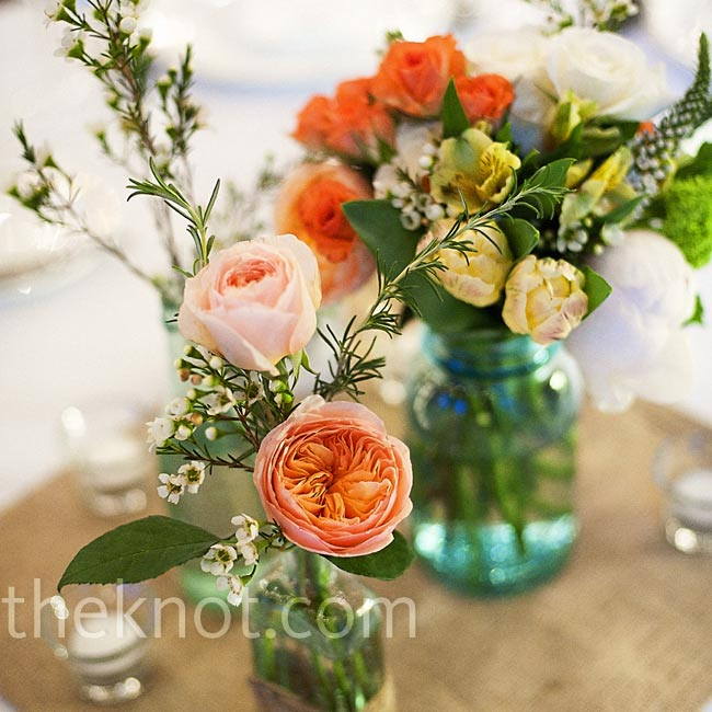 Placed on squares of burlap, aqua Mason jars and old-fashioned medicine bottles held a variety of peach, coral and yellow blooms.