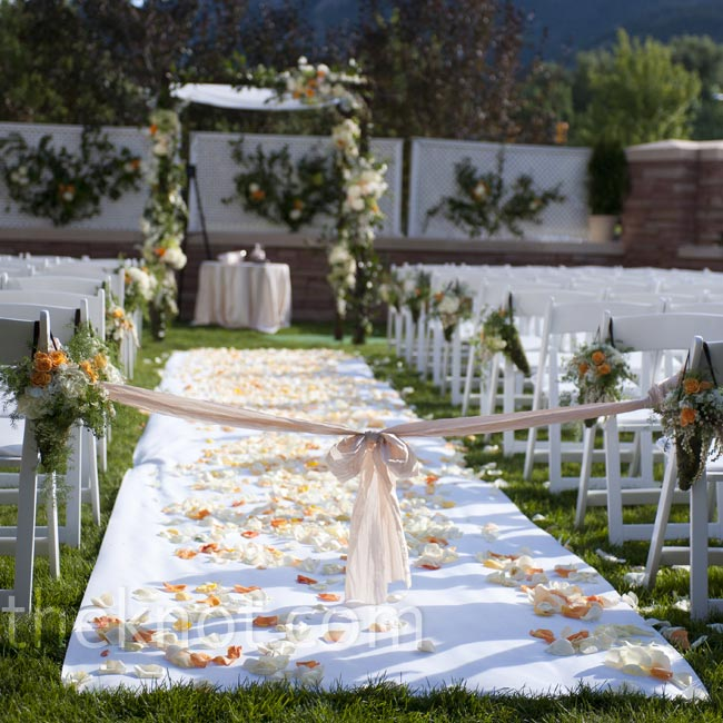 A white aisle runner was sprinkled with peach, orange and white petals.