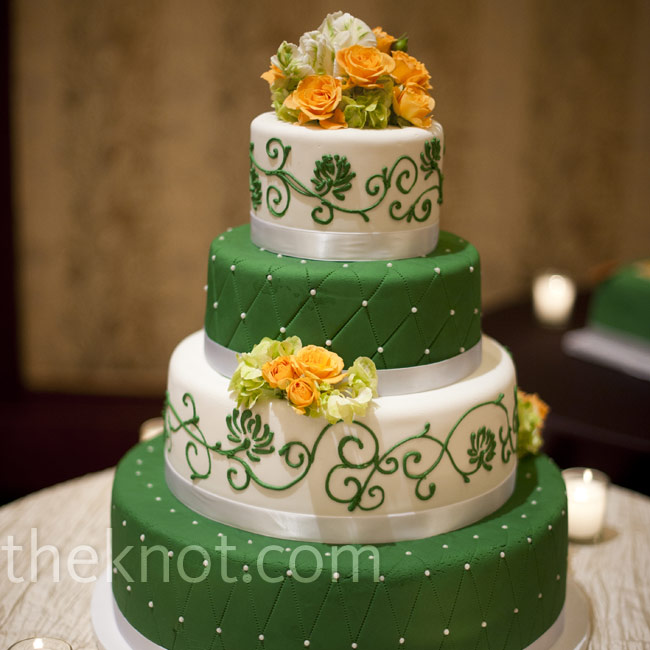 The four-tiered cake was decorated with contrasting designs on each tier and accented with peach, green and white flowers.