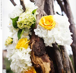Fresh yellow roses and white hydrangeas added softness to the branches that were used to create the huppah.