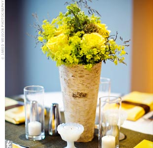 A tall, bark-covered vase held a collection of soft yellow blooms and grasses and was placed on a table runner of textured Yuma linen.