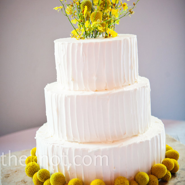 Textured lemon buttercream covered the cake, while yellow flowers lined the base and formed the topper.
