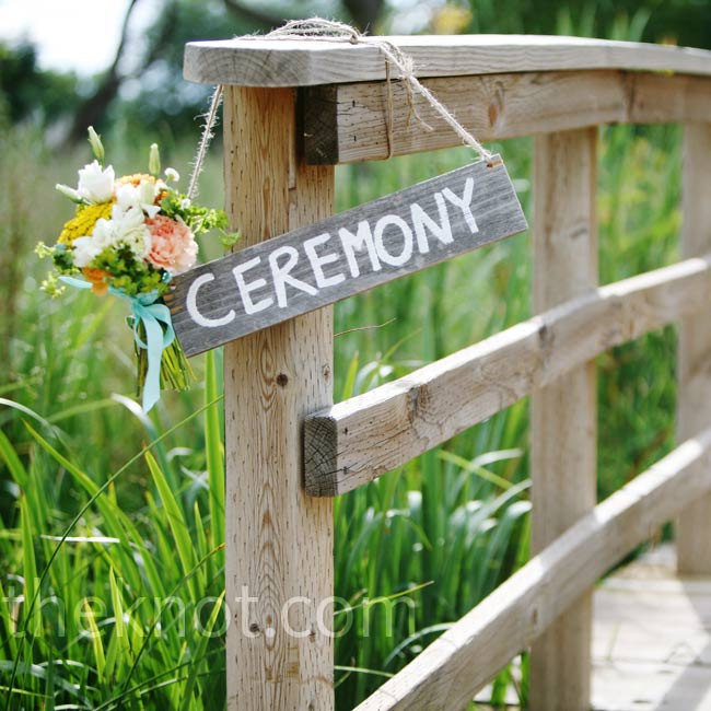 A hand-painted wooden sign decorated with a nosegay of flowers directed guests to the ceremony.