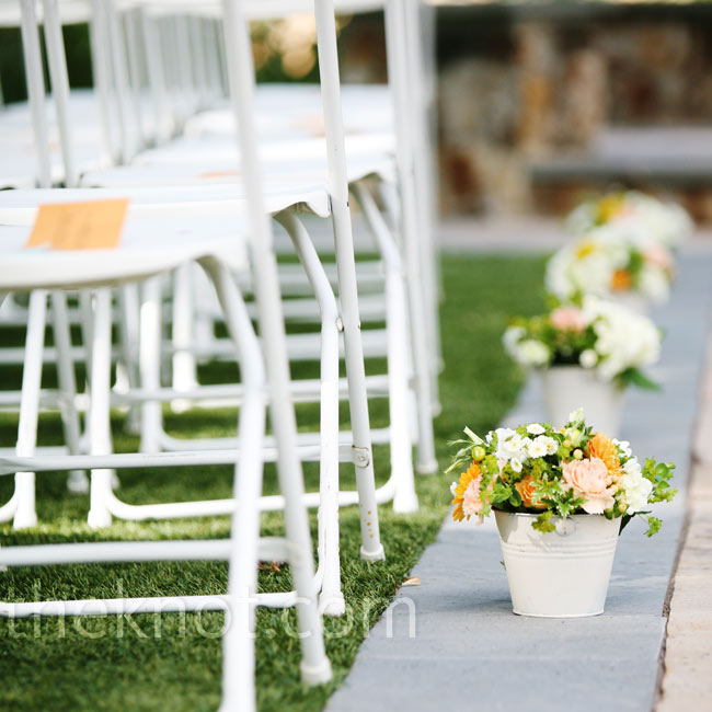 White galvanized buckets of cream, peach, yellow and green blooms lined the aisle.