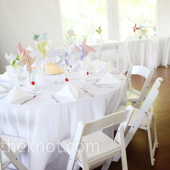 Crisp white table linens were a simple backdrop that kept the colorful pinwheels and cake centerpieces as the focus.
