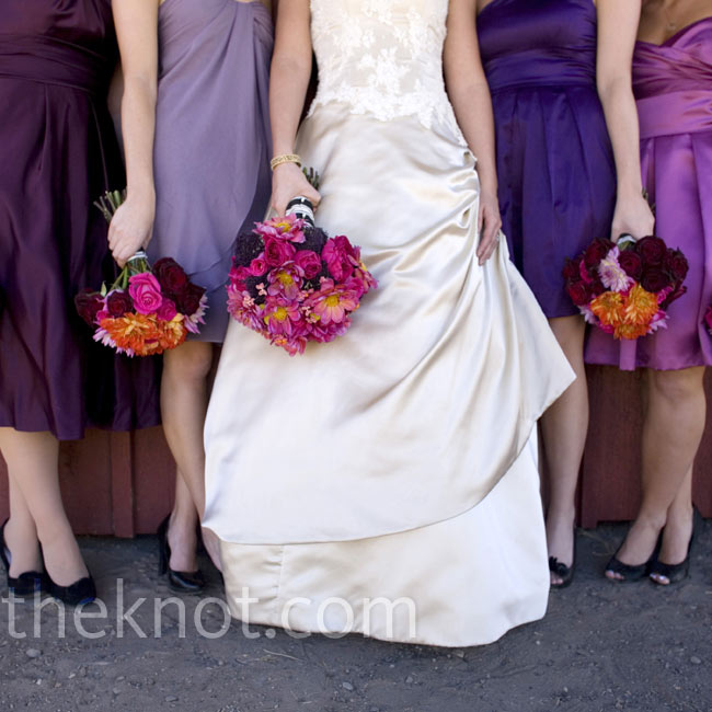 Roses and dahlias in shades of red, pink and orange complemented Lora's champagne gown and the varying shades of purple of the bridesmaid dresses.