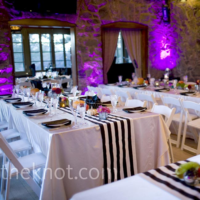 Black-and-white table runners made a bold visual impact while eerie purple uplighting brought in a hint of spookiness as a nod to the Halloween season.