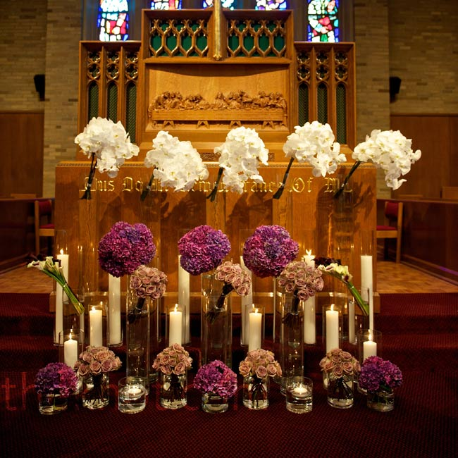 The couple wanted a contemporary look for the altar: Monobotanical, monochromatic bouquets were set in cylinder vases of varying heights and alternated with candles.
