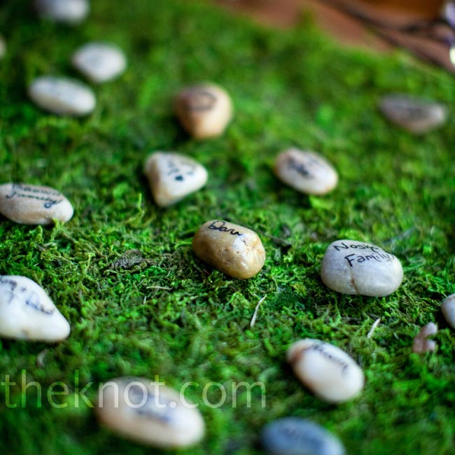 Guests' names and tables were written on rocks, which were displayed on a bed of moss.