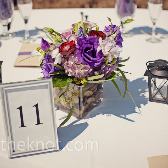 Low, square vases filled with flowers and river stones topped the tables.