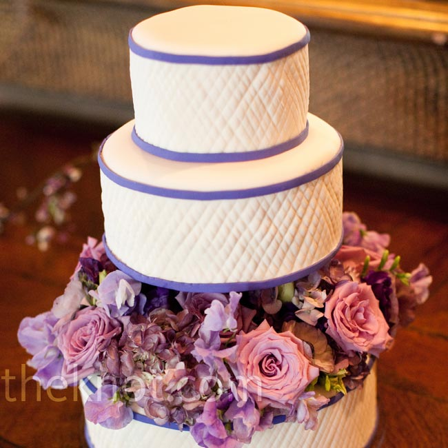 The middle and bottom tiers of the fondant cake were separated by fresh roses and other flowers.