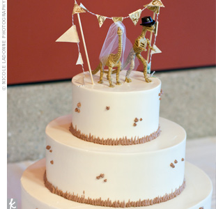 Alex and Travis opted for a simple three-tiered cake with cream cheese frosting and an unexpected bride and groom dinosaur-skeleton cake topper.