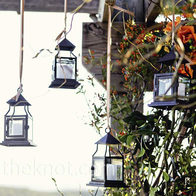 Metal lanterns hanging from the ceremony arbor brought a modern look to the floral garland.