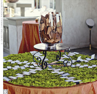 The escort cards were set on a bed of moss beneath a glass jar filled with burnt-orange paper airplanes for the couple's reception exit.