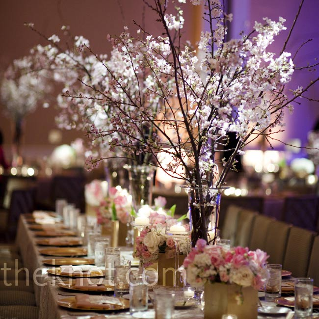 Arrangements of tall cherry blossom branches and extra candles made the head table stand out from the rest at the reception.