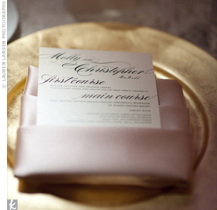 Pale-pink satin napkins tied the formal look of the gold chargers and black-and-white menu cards together.