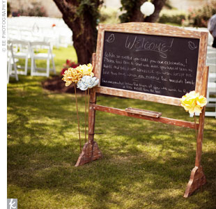 A charming chalkboard sign told guests where to sit during the ceremony.