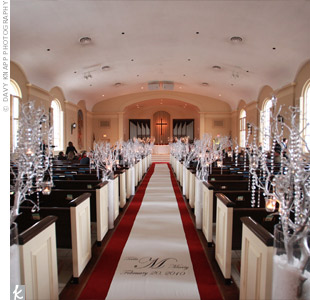The couple went all-out with aisle d&#233;cor: Silver trees draped with crystal strands stood in tall vases filled with faux snow.