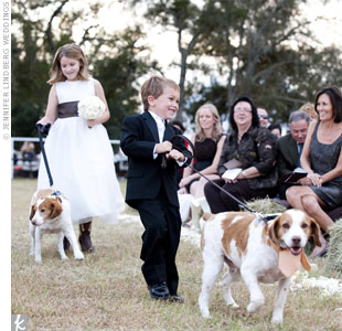 "The flower girl and ring bearer walked Callie and Kris's two dogs down the aisle. The pups got dressed up too—one in a pearl ""necklace"" and the other in a coral tie to match the groomsmen."