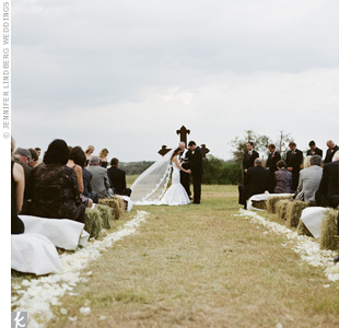 An iron cross marked the altar on the open pasture where the ceremony took place. The couple kept the décor simple with white rose petals lining the aisle. Guests sat on hay bales covered in thick fabric.