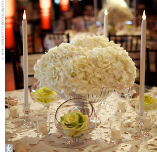 Low arrangements of white hydrangeas in silver urns surrounded by candles looked elegant, while a few glass bowls, each with a single rose, added a little glam to the tables.