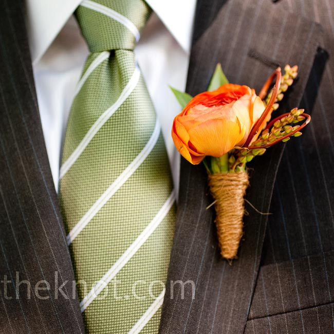 An orange-red ranunculus bud wrapped in twine complemented Loyd's sage green and white tie.