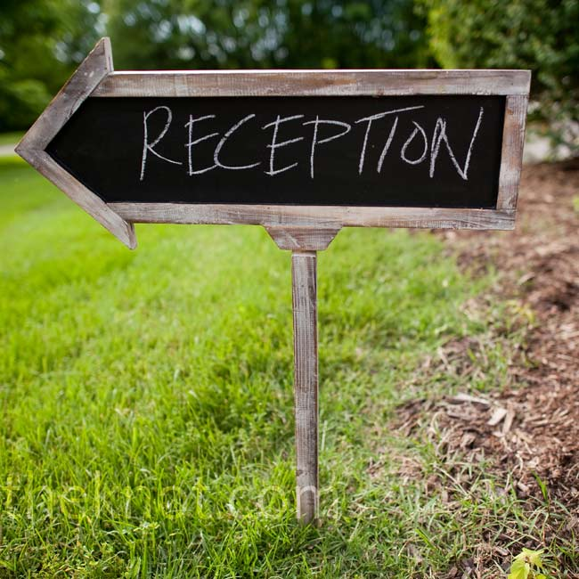 A framed chalkboard sign directed guests from the ceremony to the reception.