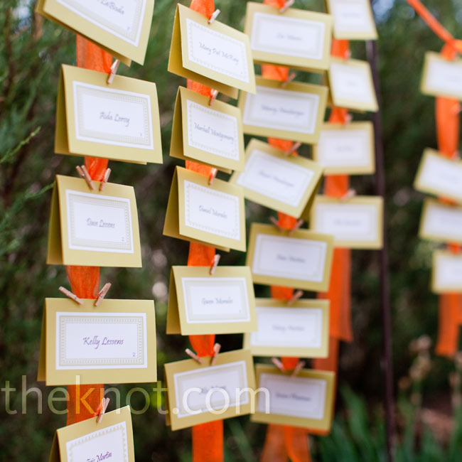 Neutral-colored escort cards were affixed to suspended orange ribbons with tiny clothespins.