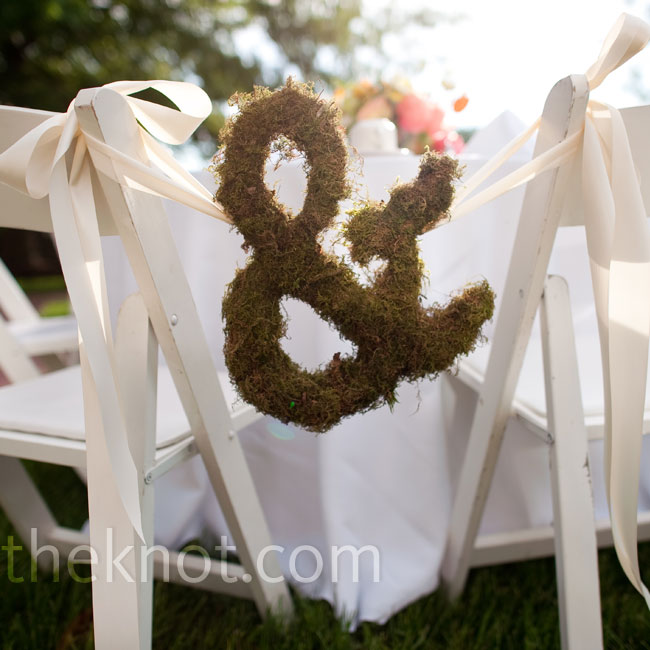A moss-covered ampersand and crisp white ribbons connected the bride's and groom's chairs.