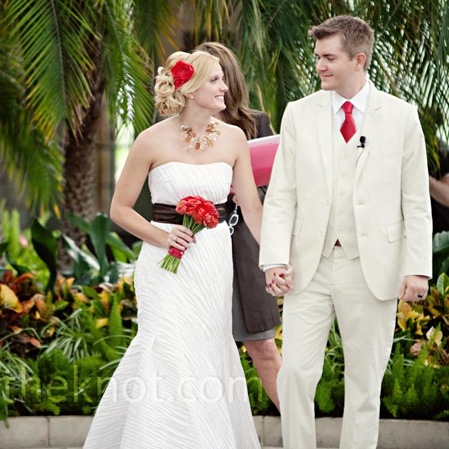 Brit chose a mermaid gown with asymmetrical pin-tuck pleats. A brown sash and rich red bouquet completed the look.