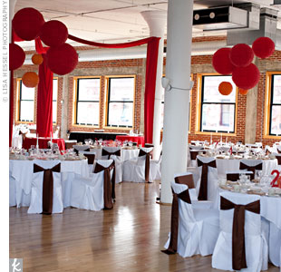 Instead of using floral décor, red fabric was draped over the dance floor while red and orange paper lanterns hung in clusters from the ceiling.
