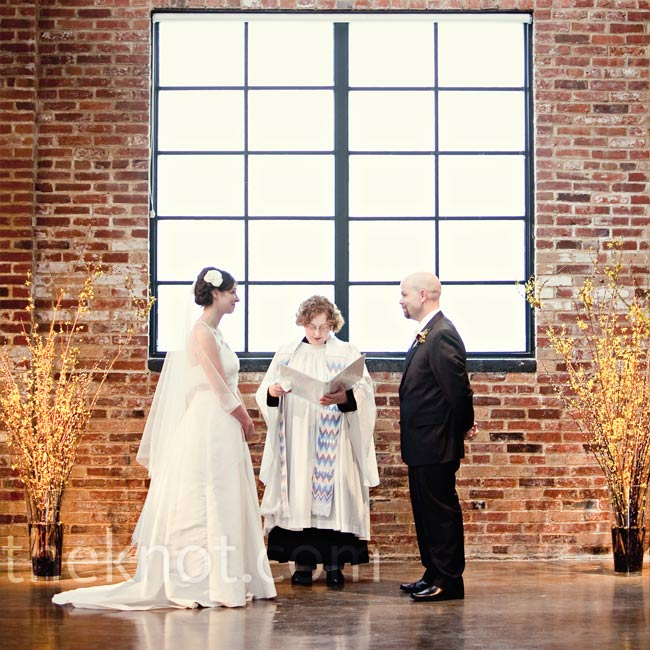 The couple exchanged vows in front of a window, while two large vases of forsythia marked the altar space.