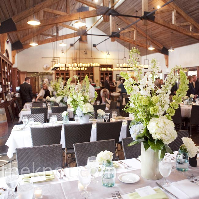 Each table was topped with a large arrangement of hydrangeas, bells of Ireland and stock with scattered blue Mason jars filled with white blooms nearby.