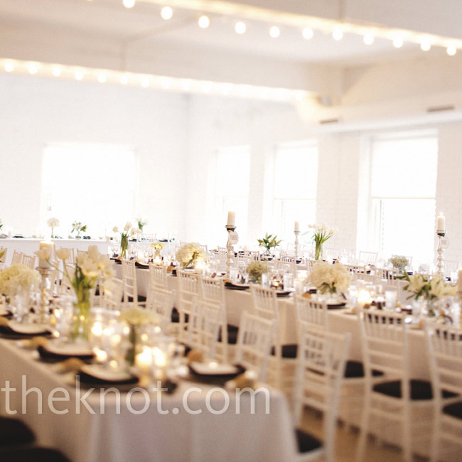 The contemporary space was arranged with long tables, white chiavari chairs, varying white floral centerpieces and silver candleholders.