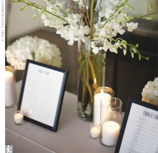 Accented by a modern floral arrangement, the seating assignments were printed and placed in black frames.