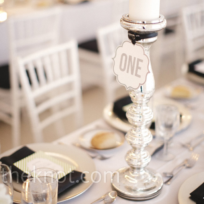 Die-cut table numbers in a bold font were attached to tall silver candleholders for a simple yet eye-catching look.
