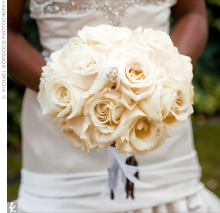 "Bola carried a classic bouquet of all-white roses with a crystal embellished ""G"" placed in the center."