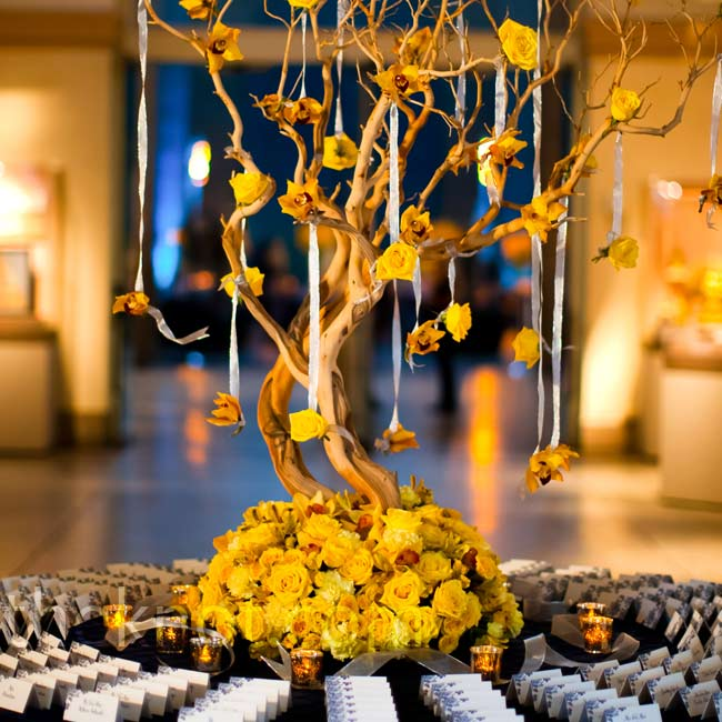The escort cards rested below a display of yellow orchids and roses hanging from manzanita branches.